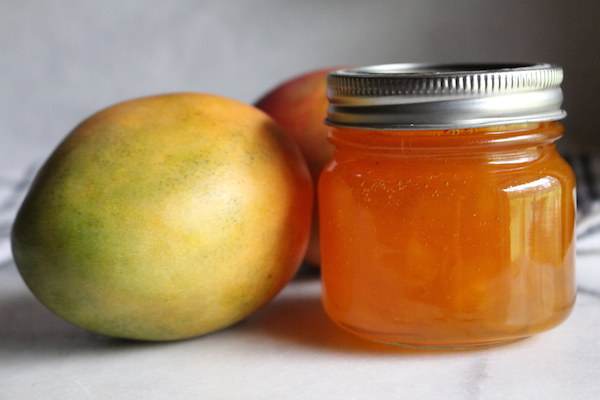 A jar of homemade mango jam sealed and shelf stable made using a canning recipe.