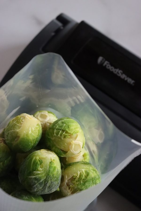 Blanched and flash frozen brussels sprouts in a vacuum sealer bag, about to be sealed with my Food Saver Vacuum Sealer.