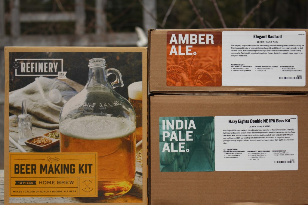 A full beer making kit including equipment (left), and two beer ingredient kits with just hops/malt/yeast (right).