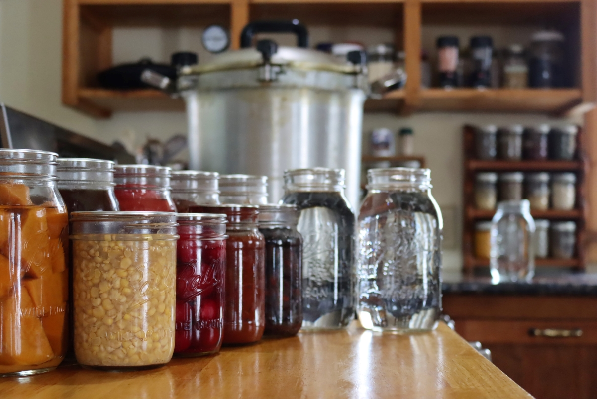 Pressure Canning ~ A display of foods that need to be pressure canned, along with a pressure canner.