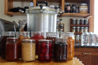 A selection of pressure canned food. Back Row (left to right): Beef Broth, Pumpkin, Tomatoes, Pinto Beans, Sweet Potato. Front Row: Pasta Sauce, Corn, Beets, Black Beans.