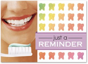 "dental reminder card with image of smiling person with toothbrush, pattern of colorful teeth silhouettes, caption reads ""just a reminder"""
