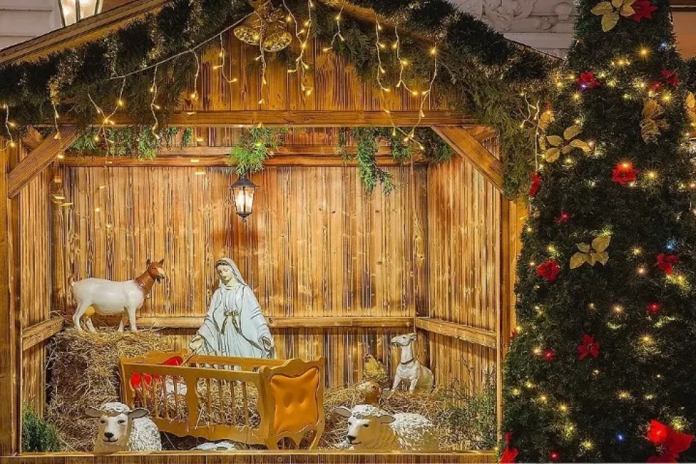 Nativity scene with Holy family of Joseph, Mary, baby Jesus Christ and sheep, holiday decorations in the Old Town in the magical city of Prague at night, Czech Republic