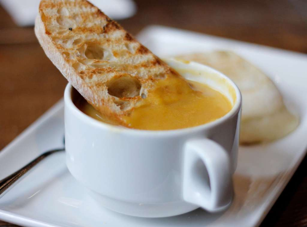A cup of butternut squash soup with a piece of toasted bread dipped in.