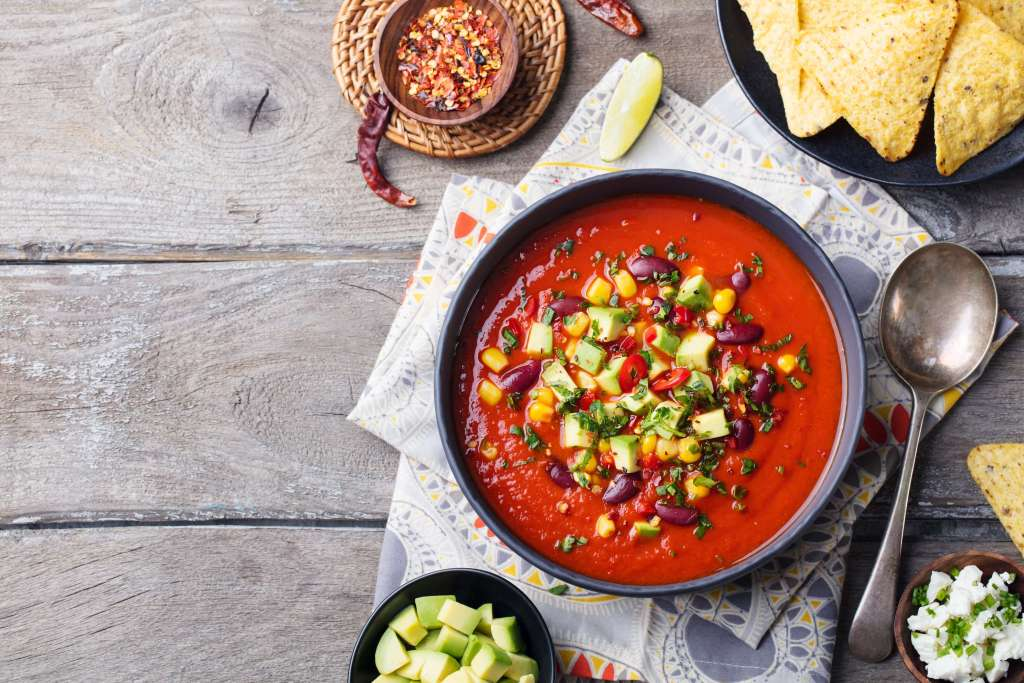 A bowl of Spicy Tomato Soup on a wooden table.