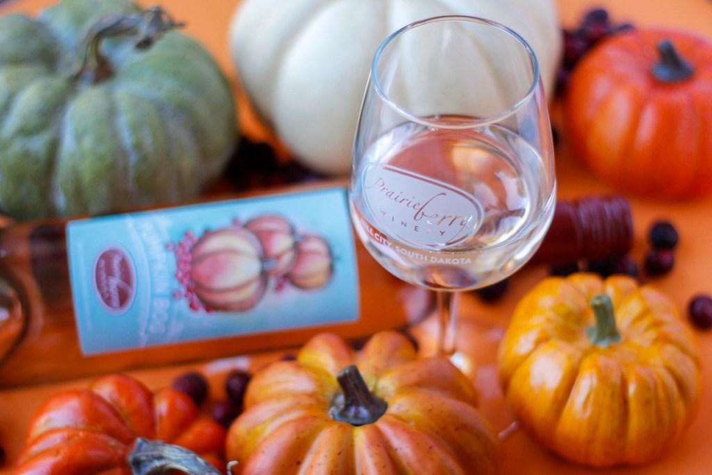 A festive fall scene featuring a glass of Pumpkin Bog wine, made in South Dakota by Prairie Berry Winery