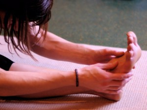 Photo: woman folds forward on a yoga mat, lightly touches foot