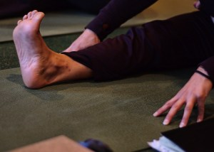 Photo:  woman seat on yoga mat, stretching forward towards foot.