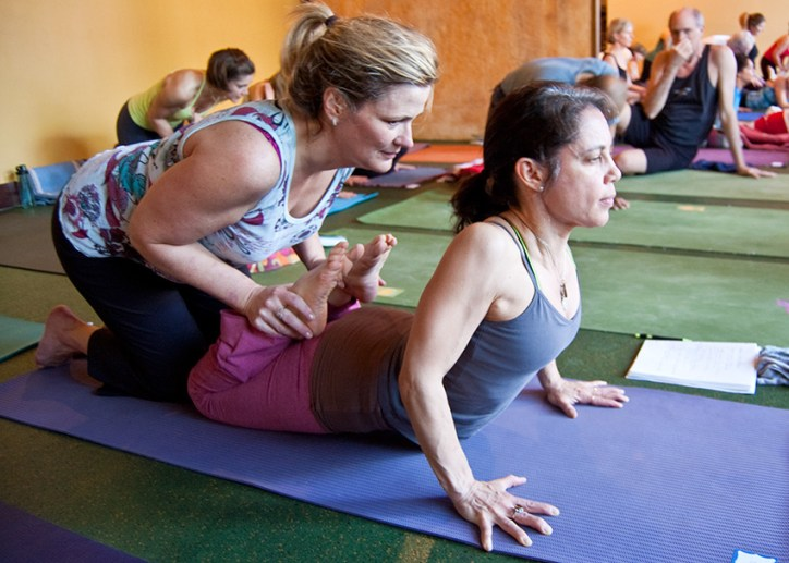 Photo: two yoginis get deeper into a pose