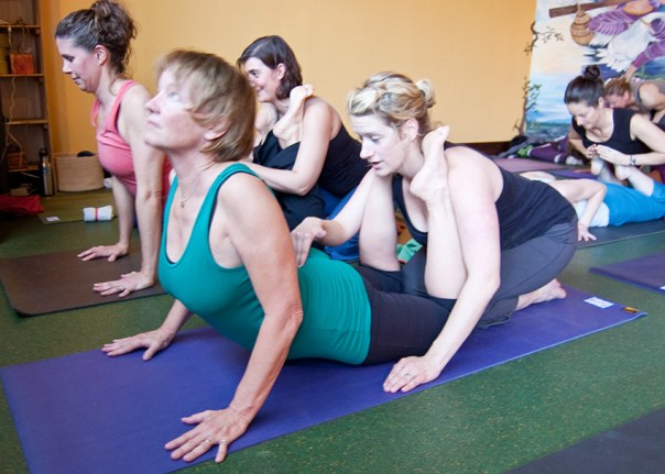 Photo: two yoginis partner to get into pose