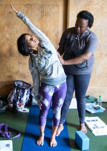 Photo: a yoga teacher adjusts a student's pose