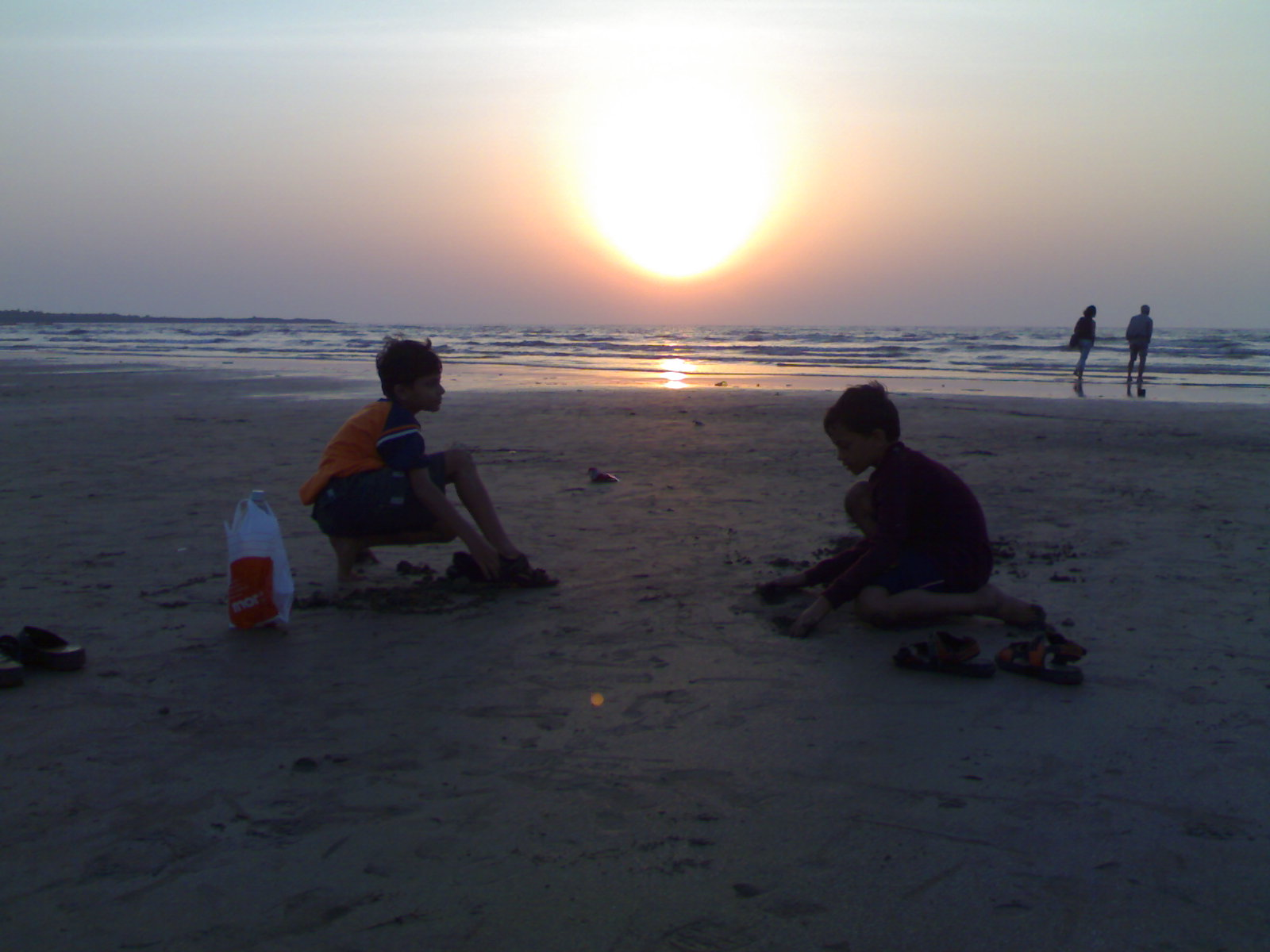 Sunset in the sands of Aksa-Bombay..Sagar,Sahil making houses on the sand, Mamta and her father walking by the sea in the horizons