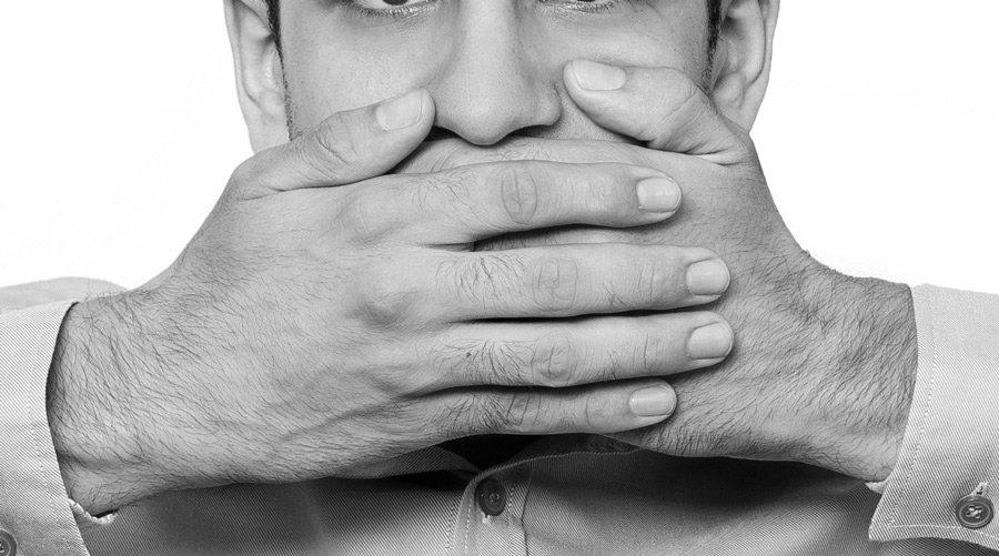 Foto em preto e branco de homem cobrindo a boca
