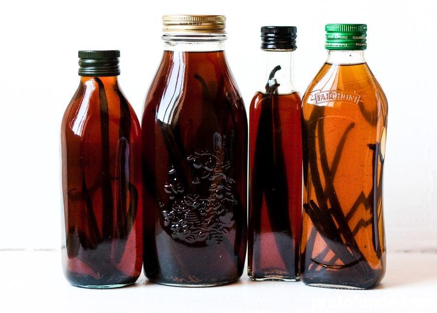 Quatro garrafas de vidro com extrato e baunilhas dentro
