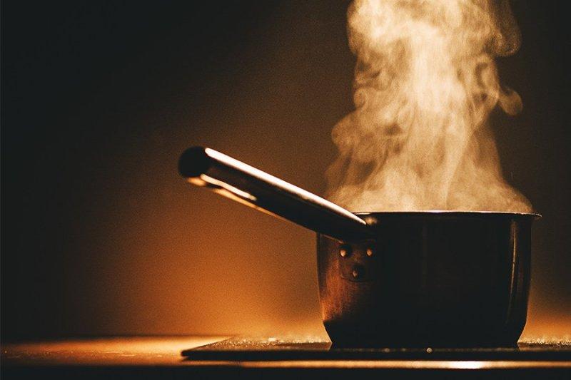 Panela com cabo com líquido fervente e vapor sobre fogão de indução em fundo escuro