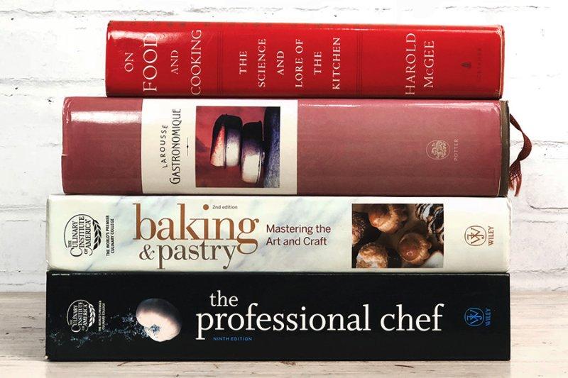 Quatros livros de gastronomia empilhados