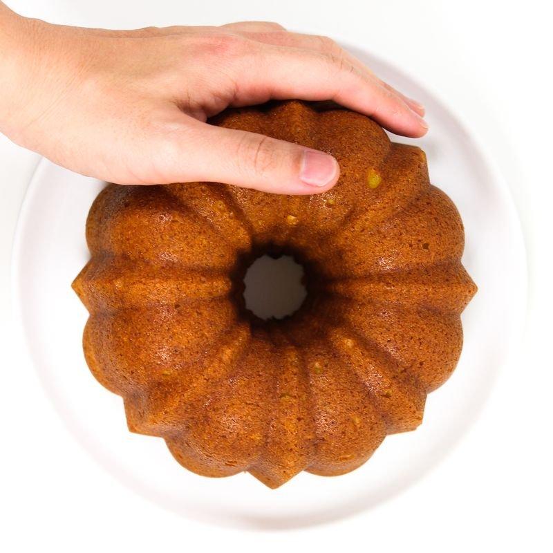 Mão de homem sobre o bolo de cenoura para mostrar a ideia de tamanho