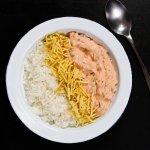 Prato feito com arroz, batata palha e estrogonofe de cogumelos sobre uma mesa visto de perto.