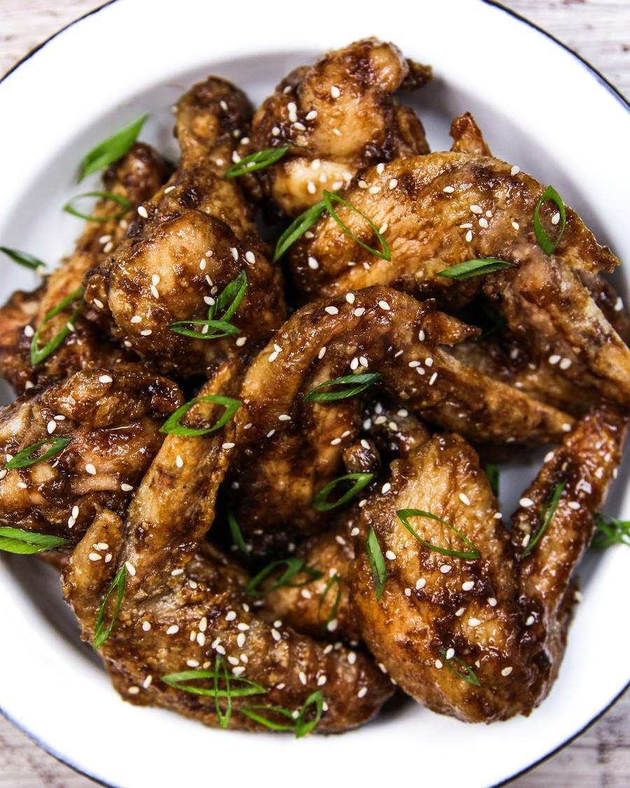 Pedaços de frango coberto com molho escuro, cebolinha e gergelim em close