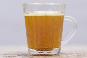 Xícara de vidro transparente com a manteiga queimada dentro, coloração dourada