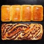 Pão estilo caseiro e pão doce recheado de maçã visto de cima sobre uma mesa.