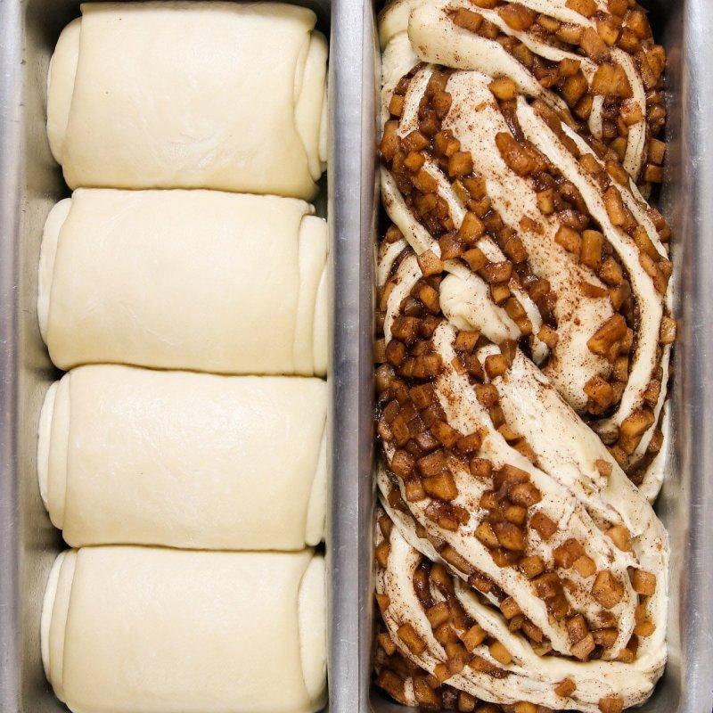 Forma com massa crua de pão, uma com massa tradicional sem recheio e a outra com recheio de maçã.