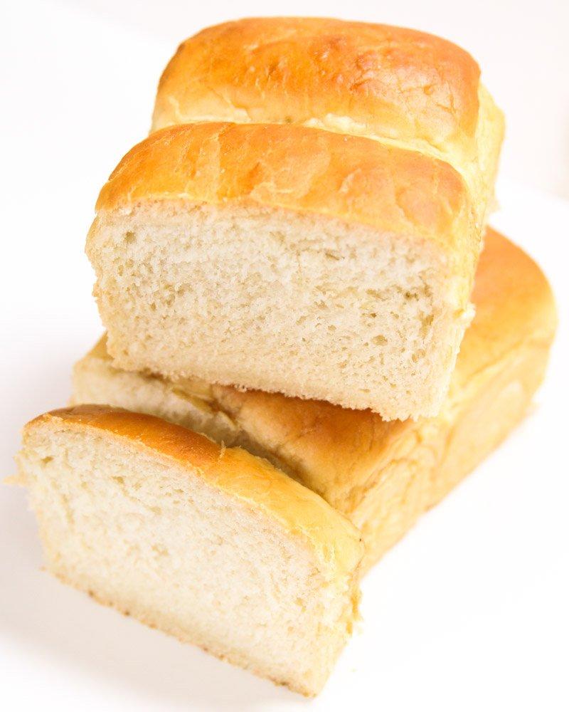 Pão estilo caseiro vegano cortado mostrando o miolo sobre uma mesa.