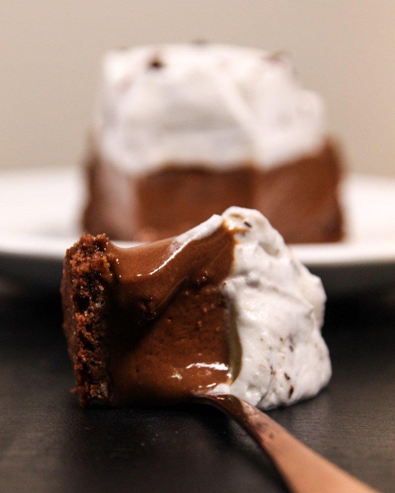 Torta mousse de chocolate em uma colher visto de frente em cima de uma mesa.