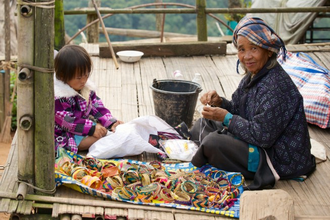 KOK DONG VILLAGE, CHIANG MAI, THAILAND - NOVEMBER 22, 2013: Unidentified woman and a girl produce traditional hill tribe souvenirs on November 22, 2013 in Doi Ang Khang, Thailand.