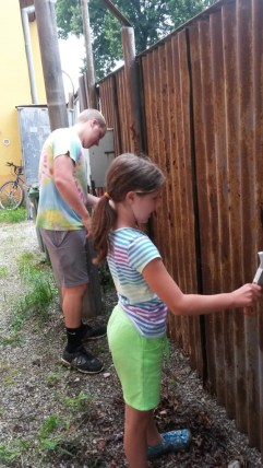 Scraping rust and dirt off the fence (Roma School in Kezmarok).