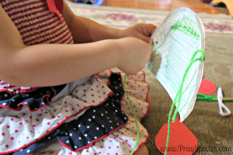 threading the paper plate with yarn