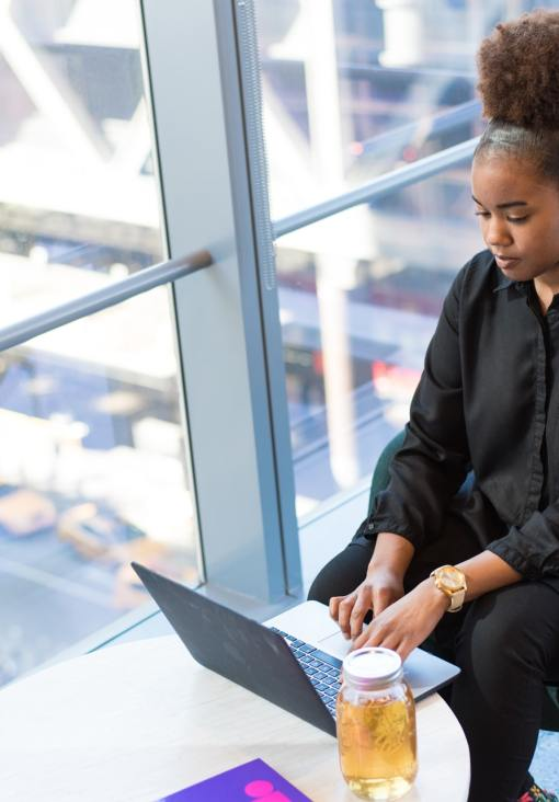 image of beautiful black woman in dress shirt using laptop
