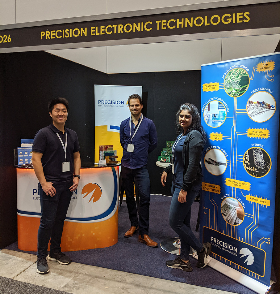 Precision team standing in front of company banners displayed at their booth