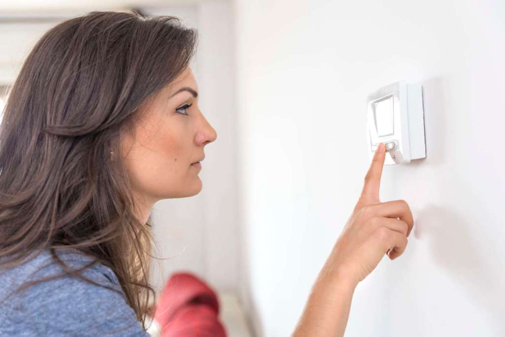 Woman setting furnace thermostat