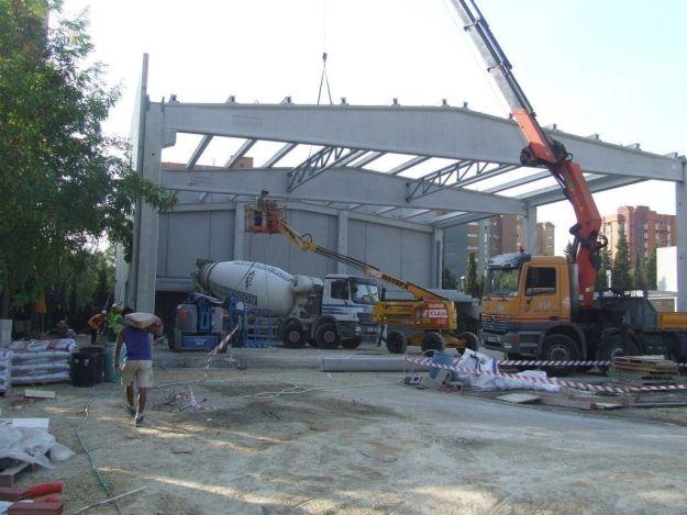 Operarios de montaje con EPI reglamentario y de constructora sin