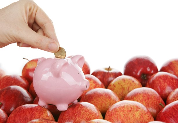A hand putting a coin in a piggy bank sitting on apples.