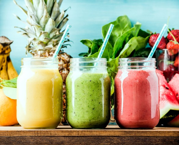 Freshly blended fruit smoothies of various colors and tastes in open mason jars with straws