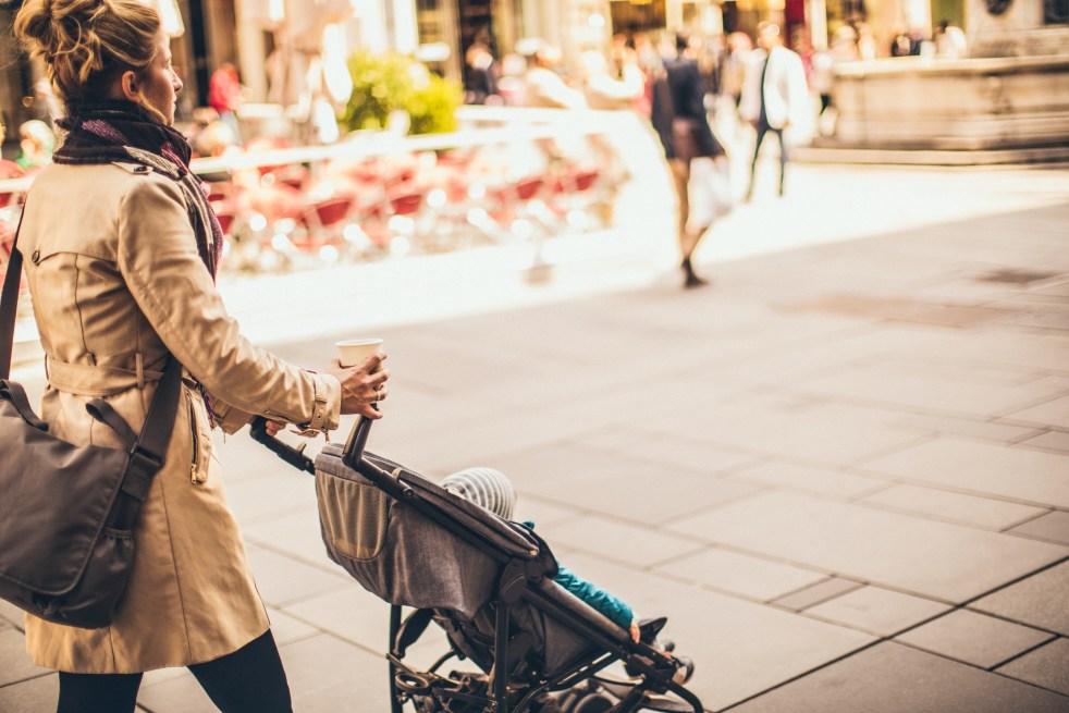 Parent pushing stroller on sidewalk