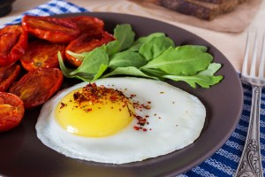 Plated fried egg with side of salad and roasted tomatoes
