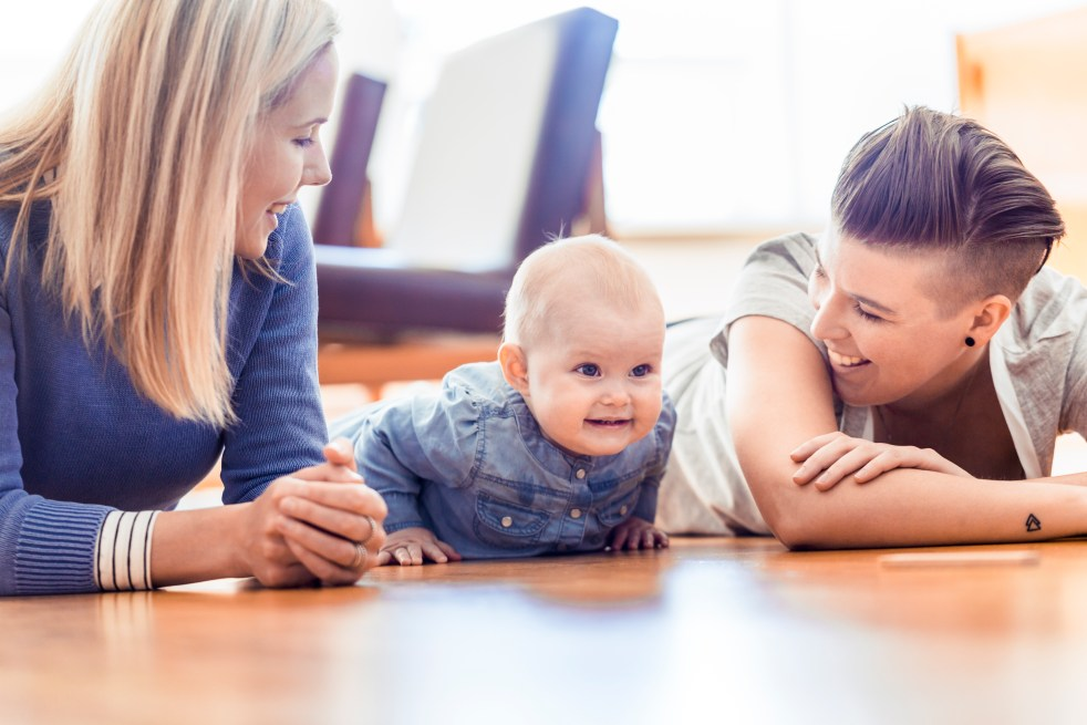 Smiling parents and baby lying on tummy on hardwood floor
