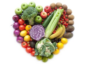 Fruits and vegetables in a heart shape over a white background