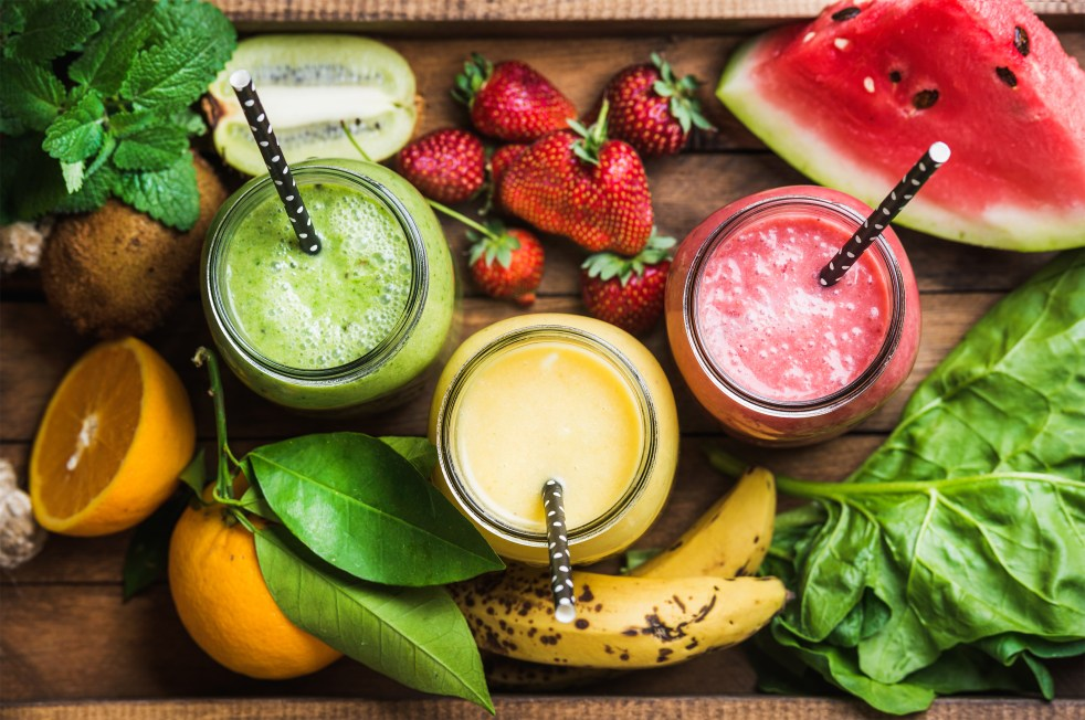 Freshly blended fruit smoothies of various colors and tastes in glass jars in rustic wooden tray. Yellow, red, green.