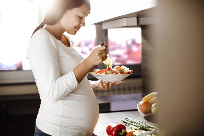 Expectant parent eating healthy food in a white bowl