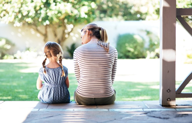 Rearview shot of a parent sitting beside her daughter having a conversation on the porch
