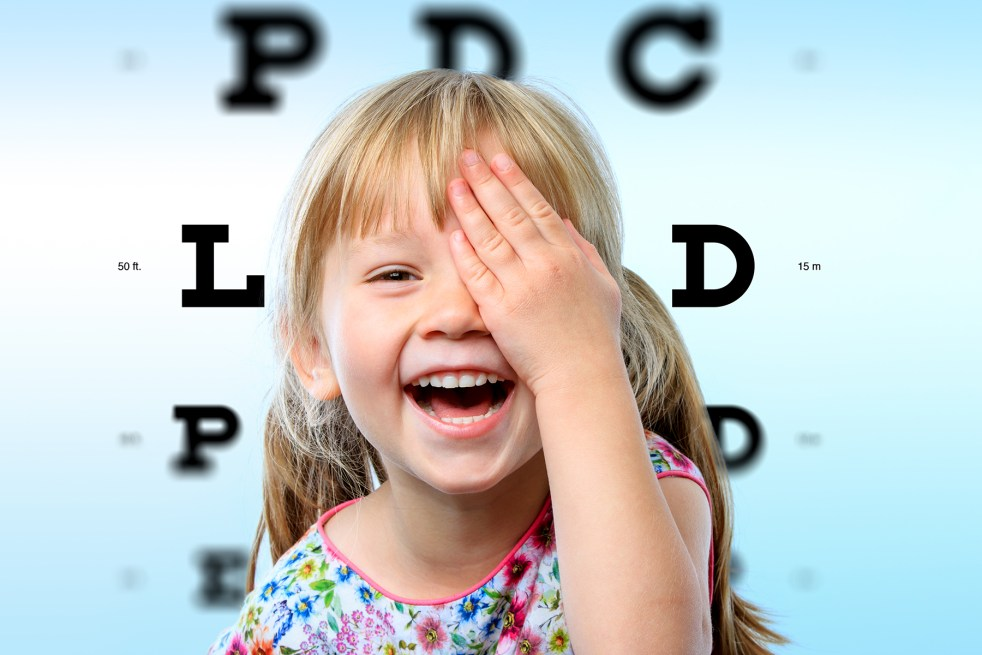 girl closing one eye with hand and block letter eye chart in background.