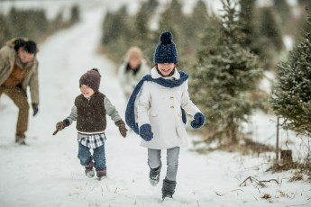 family is outdoors at a Christmas tree farm during winter. They are wearing warm coats and hats. The kids are running away from their father, who is getting ready to throw a snowball.