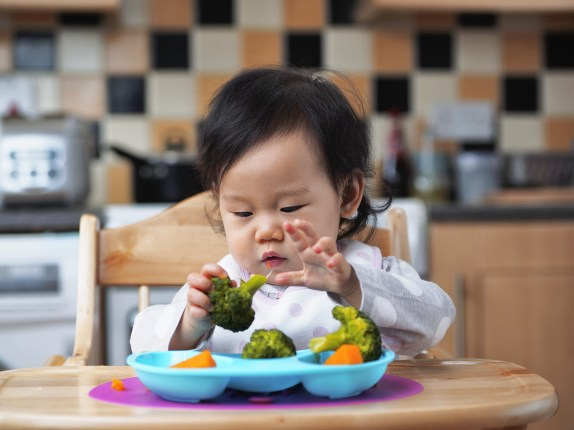 young toddler picking up vegetables from a sectioned blue plate