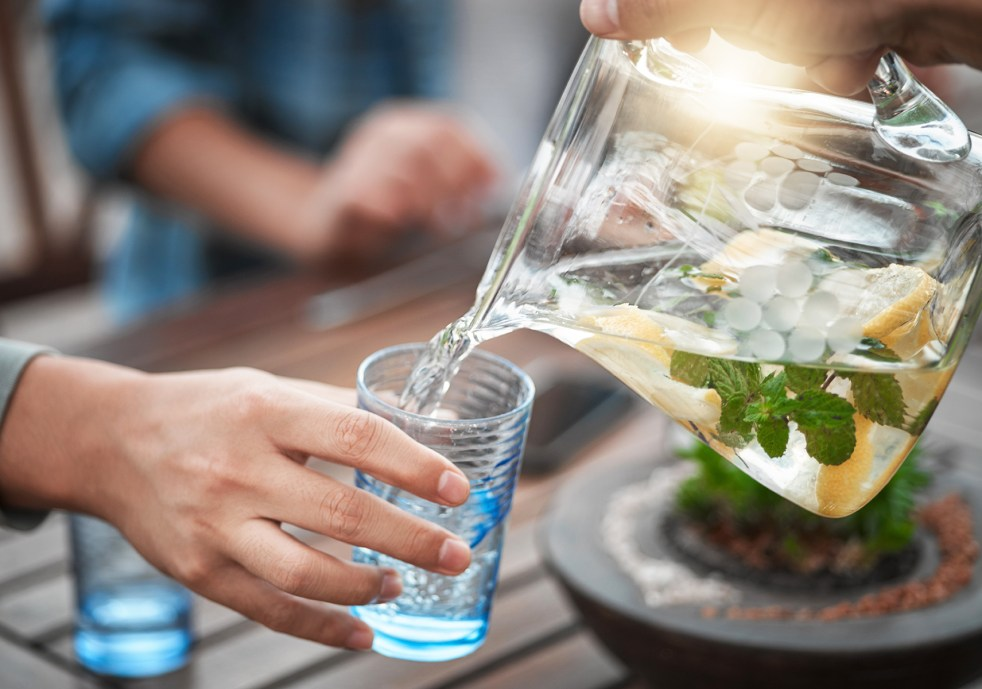Person pouring water from a pitcher into a glass outside around a table