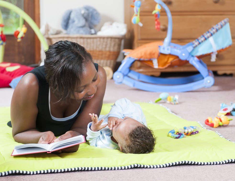 Storytime on the playmat with parent and baby in an indoor setting. parent is face to face with baby
