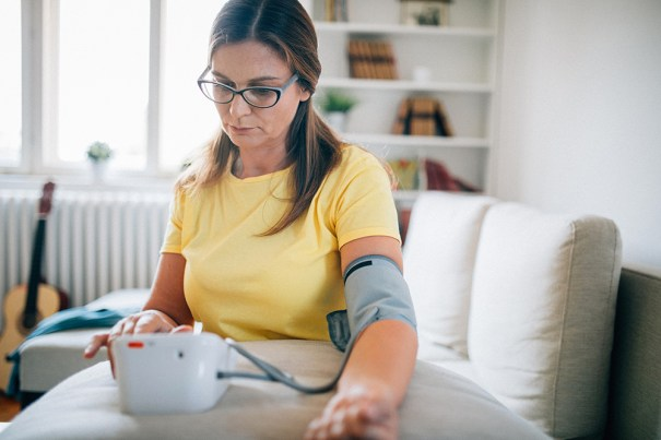 Individual checking blood pressure on a home monitor
